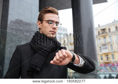 Young business man looking at wristwatch on the street