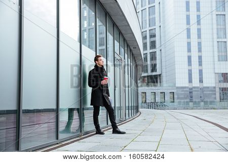 Full length business man in warm clothes holding coffee in hand on the street and looking away. Side view