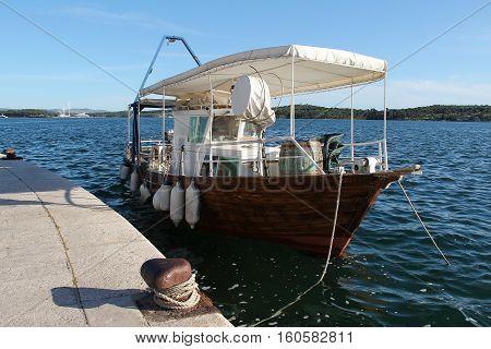Small boat attached to granite dam / Sibenik (Croatia).