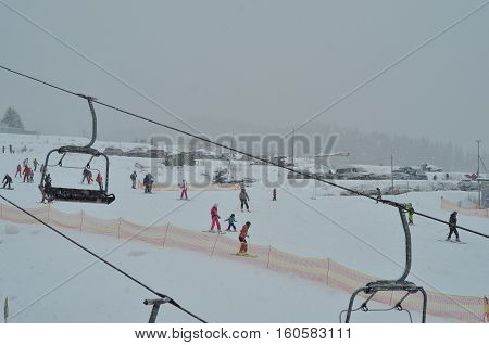 BUKOVEL, UKRAINE - December 2, 2016: Snowboarder and skiers enjoying on slopes of ski resort Bukovel. Bukovel is the most popular ski resort in Ukraine. Ski season and Winter sports concept