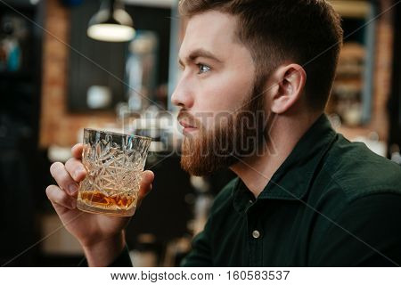 Photo of young man sitting in armchair and drinking whiskey . Look aside.