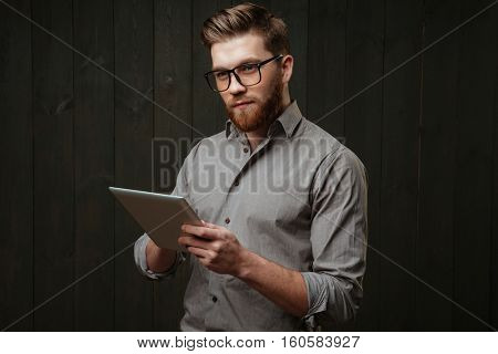 Portrait of a handsome bearded man in eyeglasses holding tablet computer and looking away isolated on the black wooden background