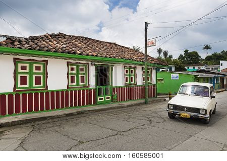 Salento Colombia - February 10 2014: An old car in a street of the town of Salento in Colombia with an old colorful colonial house;