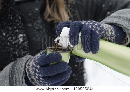 Closeup of female hands in knitted gloves pouring hot coffee from a thermos on a winter cold snowy day