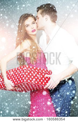 Beautiful fond young couple standing close to each other holding big spotted red present box vertical photo