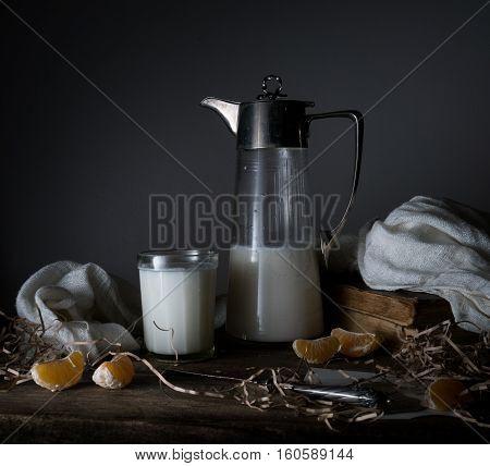 still life. tangerines, tangerine slices, old milk jug, glass of milk on a wooden table.