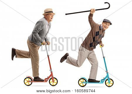 Full length portrait of two overjoyed seniors riding scooters isolated on white background