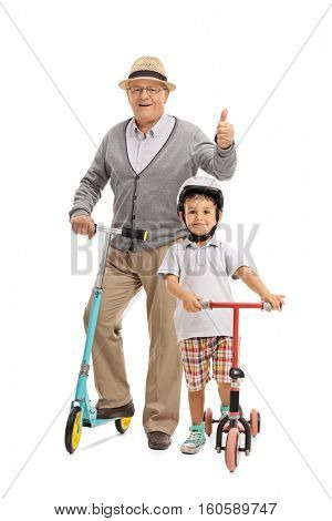 Full length portrait of a mature man with a scooter giving a thumb up and a boy with a scooter isolated on white background