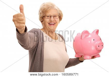 Cheerful senior holding a piggybank and making a thumb up sign isolated on white background