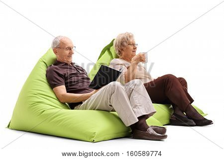 Elderly man sitting on a beanbag and reading a book with an elderly woman sitting on a beanbag and drinking from a cup isolated on white background