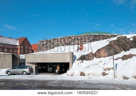 HELSINKI, FINLAND - MARCH 13, 2010: People near the enter of Temppeliaukio Church (Church of the Rock) on Lutherinkatu. Was built directly into solid rock and opened in 1969.