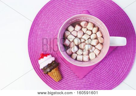 Cup of hot chocolate with sweet marshmallows on a pink placement with ice cream cone magnet. A friendship quote painted on the cup. Natural light. Isolated on white. Flat lay.