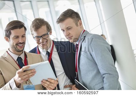 Happy businessmen using digital tablet at convention center