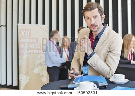 Portrait of confident businessman holding smart phone during coffee break in convention center
