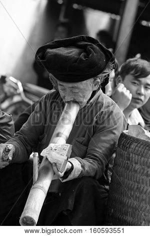 HA GIANG, VIETNAM - FEB 17, 2014: Unidentified old Vietnamese Hmong woman smoking at a weekly traditional flea market in Meo Vac province, far north of Vietnam.