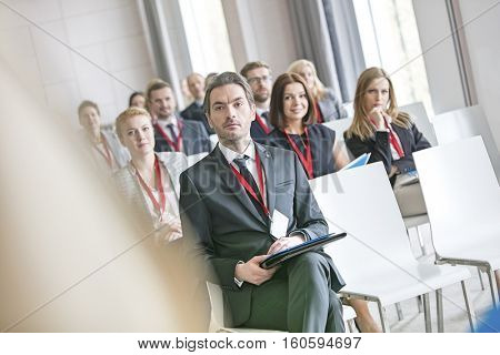 Businessman looking at public speaker during seminar in convention center