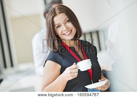 Portrait of happy businesswoman holding coffee cup in seminar hall