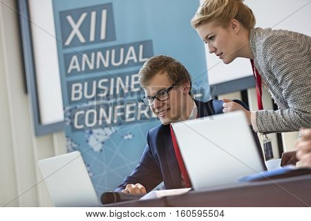 Business people using laptop in seminar hall