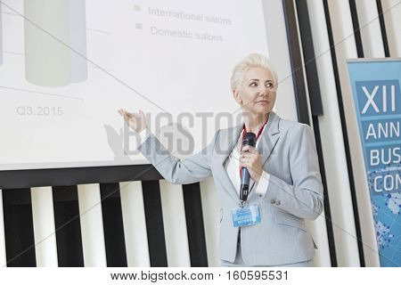 Businesswoman explaining strategy on projection screen at convention center