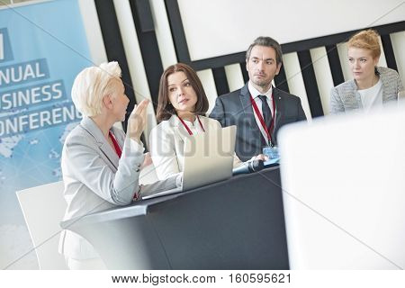 Business people talking while sitting at desk in seminar hall