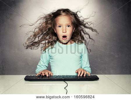 Surprised little girl with computer keyboard. Child looking at computer