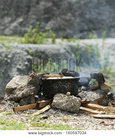 Vietnamese Thais woman cooking rice outdoor in a traditional way under the sunlight in a mountain area, north west of Vietnam.
