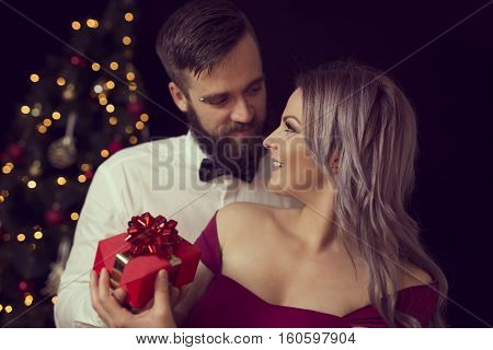 Beautiful young couple in love hugging and exchanging Christmas gifts
