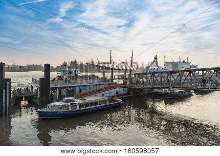 Hamburg, Germany - November 01, 2015: Tourists embark for the last harbor tour at the famous gangways of the harbor of Hamburg and enjoy a scenic sundown.