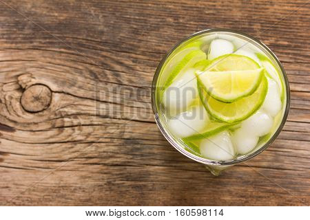 refreshing lemonade with green lemon and ice closeup top view