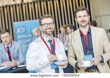 Portrait of confident businessmen holding coffee cups at lobby in convention center