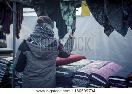 Woman shopping in the traditional market. Woman search for textile materials.