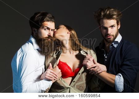 Young people or friends of two bearded handsome men hipsters with beards and pretty cute girl or sexi beautiful woman in red bra on grey wall