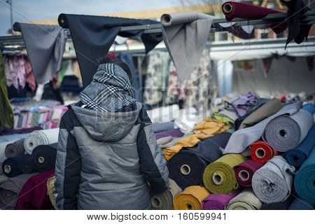A young woman is searching textiles materials in a street market.