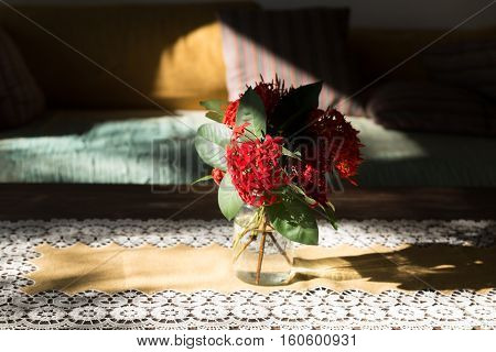 Ixora Flower On Wood Table And Brown Sofa Couch In Living Room