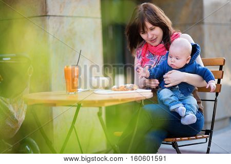 Young Mother With Her Little Son Having Breakfast