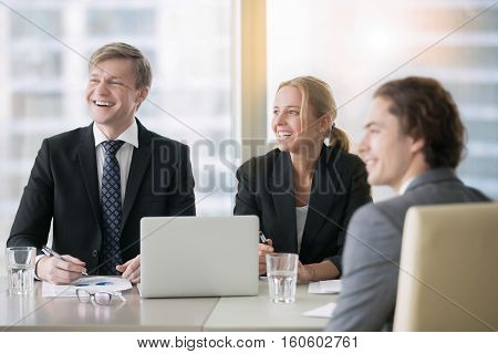 Group of three business partners discussing new project at meeting in office room, attending presentation, laughing, friendly and fun atmosphere during business discussion. Business success concept