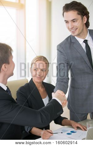 Portrait of young confident business man introducing himself at business meeting to his partners. Three smiling businesspeople in suits making agreement, greeting each other, shaking hands. Indoor