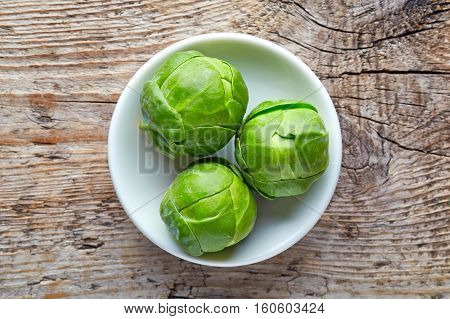 Bowl Of Brussels Sprouts On Wooden Table, From Above