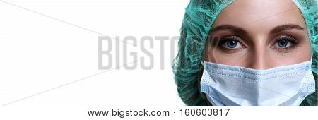 Female doctor face wearing protective mask and green surgeon cap closeup isolated on white background. Save patient life copy space banner laboratory 911 medic help concept. Letterbox view
