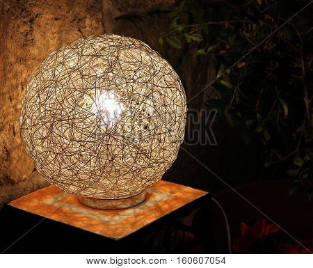 A modern lamp made from intertwined metallic wires on a table outside.