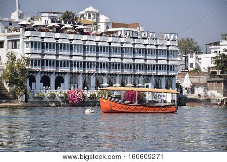 UDAIPUR, RAJASTHAN, INDIA, FEBRUARY 07, 2016 - Buildings and an orange boat along Pichola lake
