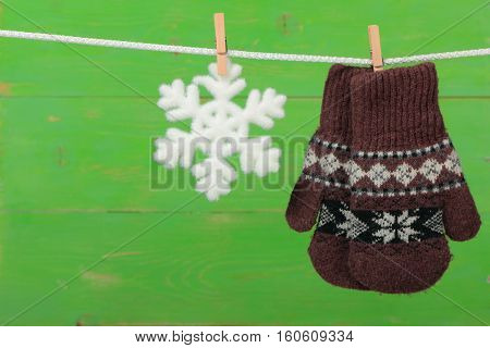 Mittens with snowflakes hanging on the clothesline on green wooden background