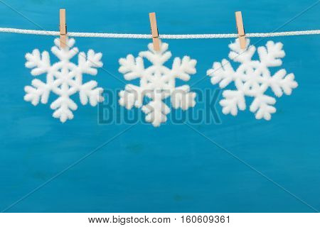 Christmas baubles in shape snowflake on blue wooden background