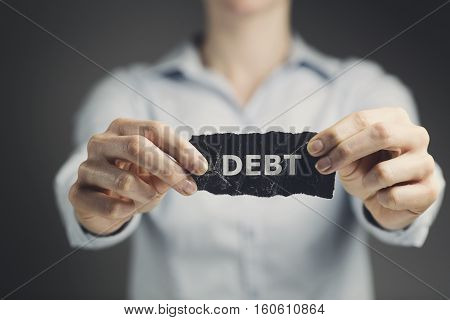 Woman holding a label with the word debt toward the camera. Shallow DOF, focus on the label.