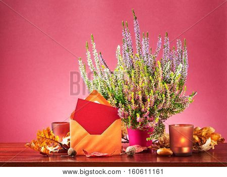 Autumn mail. Still life with greeting card envelope heather flowers in flowerpot dry leaves and candles