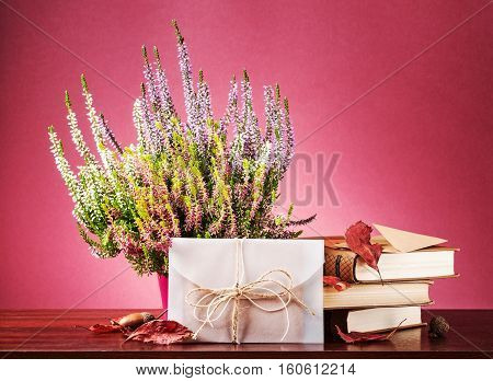 Autumn surprise. Still life with closed white envelope heather flowers dry leaves and books