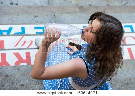 Young woman with blue polka dot dress sitting on steps drinking carbonated water in a clear bottle
