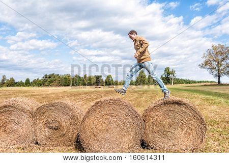 Young man jumping over hay roll bales in a field