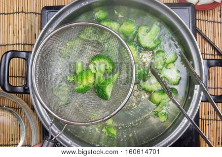 Chef boiling Broccoli in pan / cooking spicy spaghetti concept