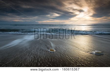 Pebbles on the beach on a black sand and flowing sea waterduring sunset. Long exposure image.